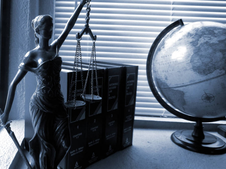 Lady Justice sitting on a desk with a background of books and a globe.