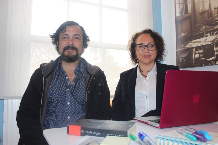 Roberto Bruna and Ana Arriagada sitting at a desk for a photo.