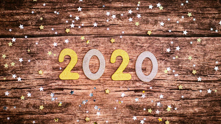 """2020"" numbers laid over a wooden table with stars scattered around."