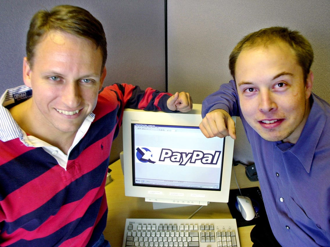 Picture of Peter Thiel and Elon Musk sitting around a computer, founders of PayPal.