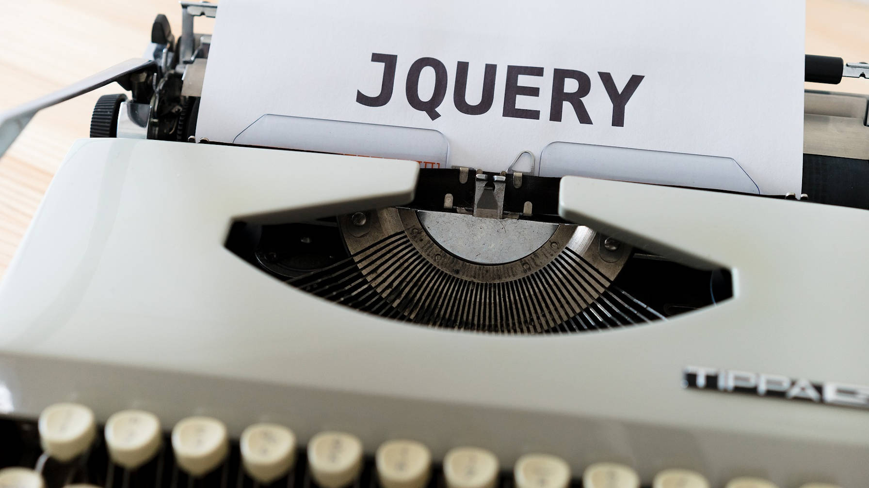 "Decorative image of a typewriter with the word ""jQuery"" typed on a sheet of paper."