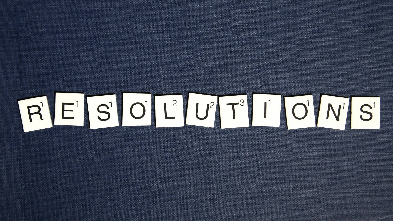 "Scrabble tile pieces spelling ""resolutions"" set atop a blue fabric background."