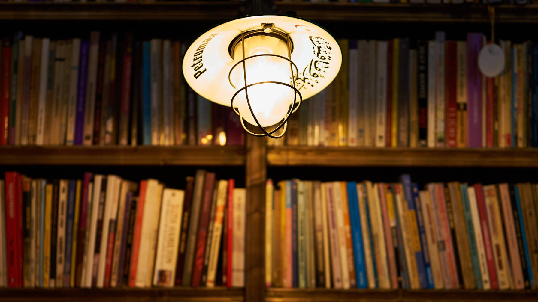 Shelves filled with books with a hanging light in front, illuminating them.
