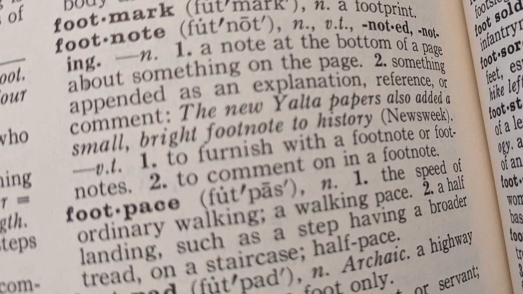 "Decorative image of a page in a dictionary, highlighting the ""footnote"" definition."
