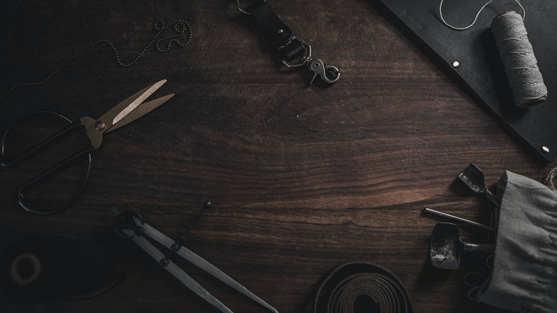 Decorative image of a wooden desk with various tools lying on it.